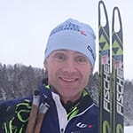A man in a toque holds his skis