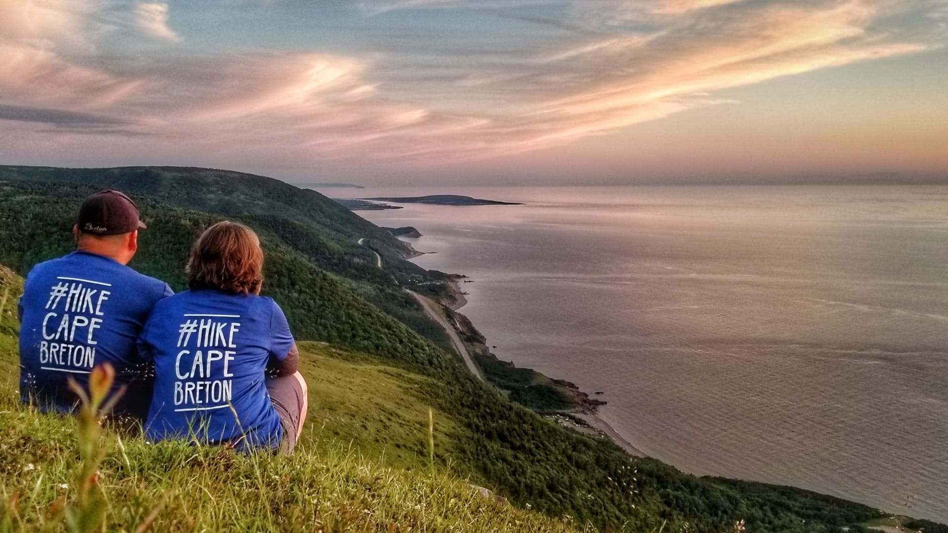 A couple sit on a grassy hill overlooking the ocean wearing shirts that say #HikeCapeBreton