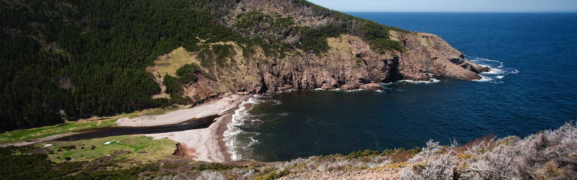 A small beach sits between two rocky coasts