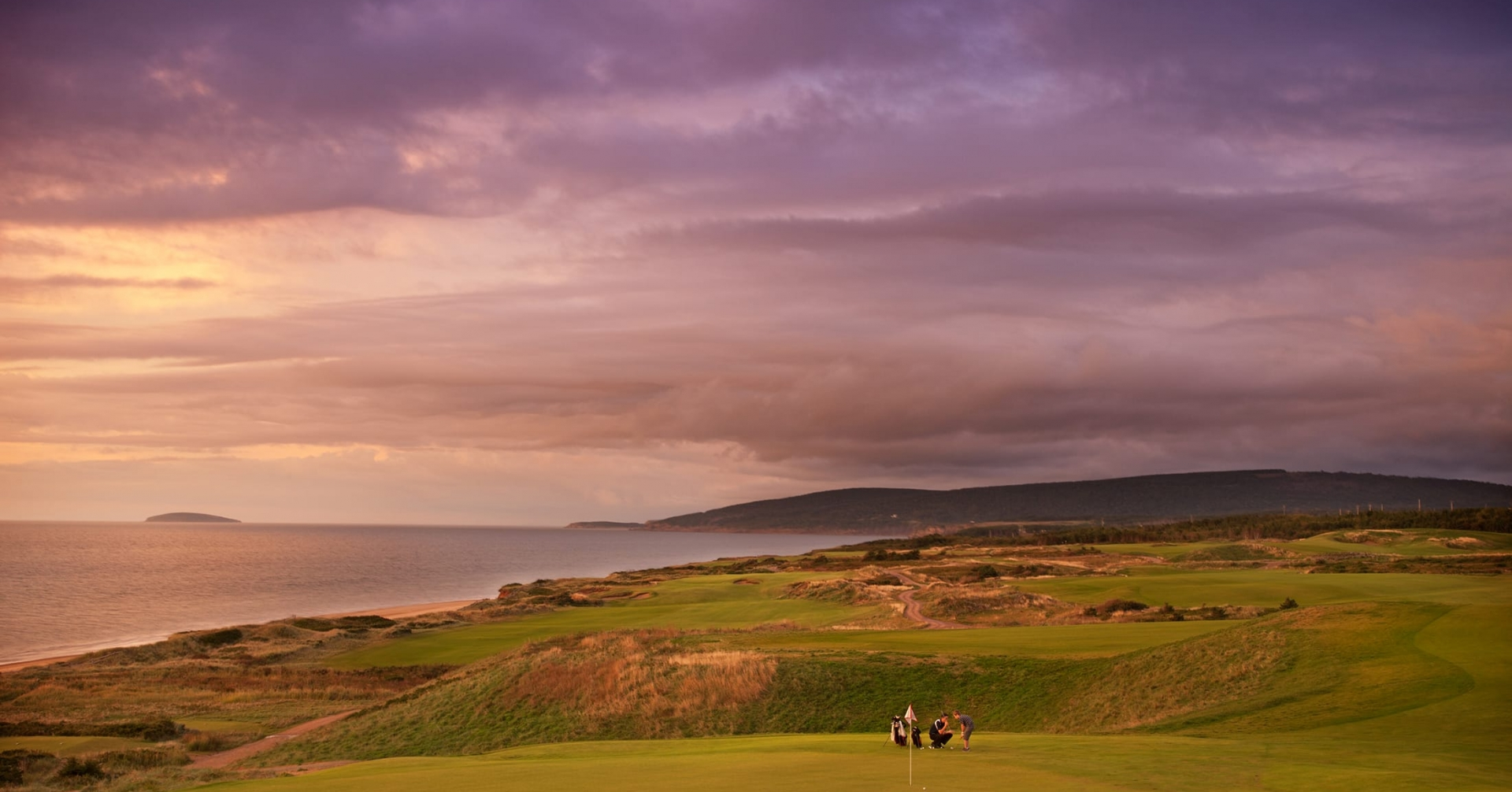 A golf course overlooking the ocean at sunset