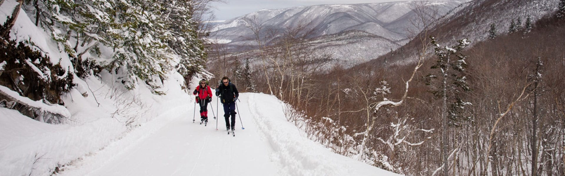 A couple cross country ski with snowy mountains in the background