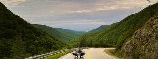 A motorcycle travels down a highway in a rolling green landscape