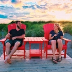 A man and woman sit in adirondack chairs on the beach