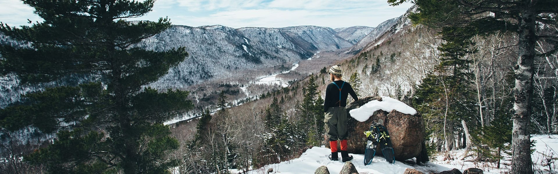 A man and his snowshoes stand next to a rock overlooking a snowy landscape