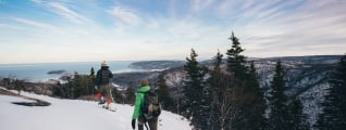 Two snowshoers trek through a snowy landscape overlooking the ocean