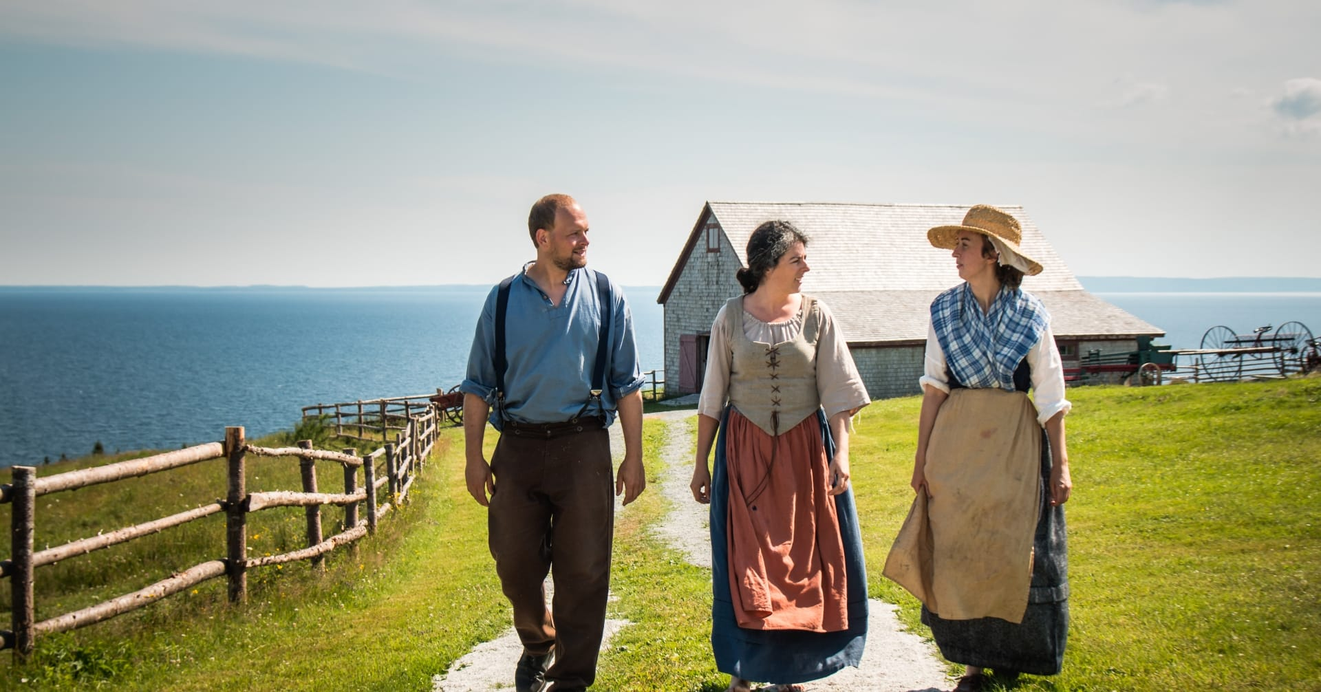 Three people in period clothing walk outside with the ocean in the background