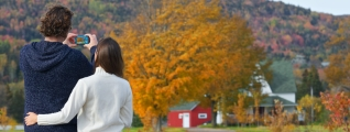 A couple stops to take a photo of a beautiful b&b surrounded by autumn foliage