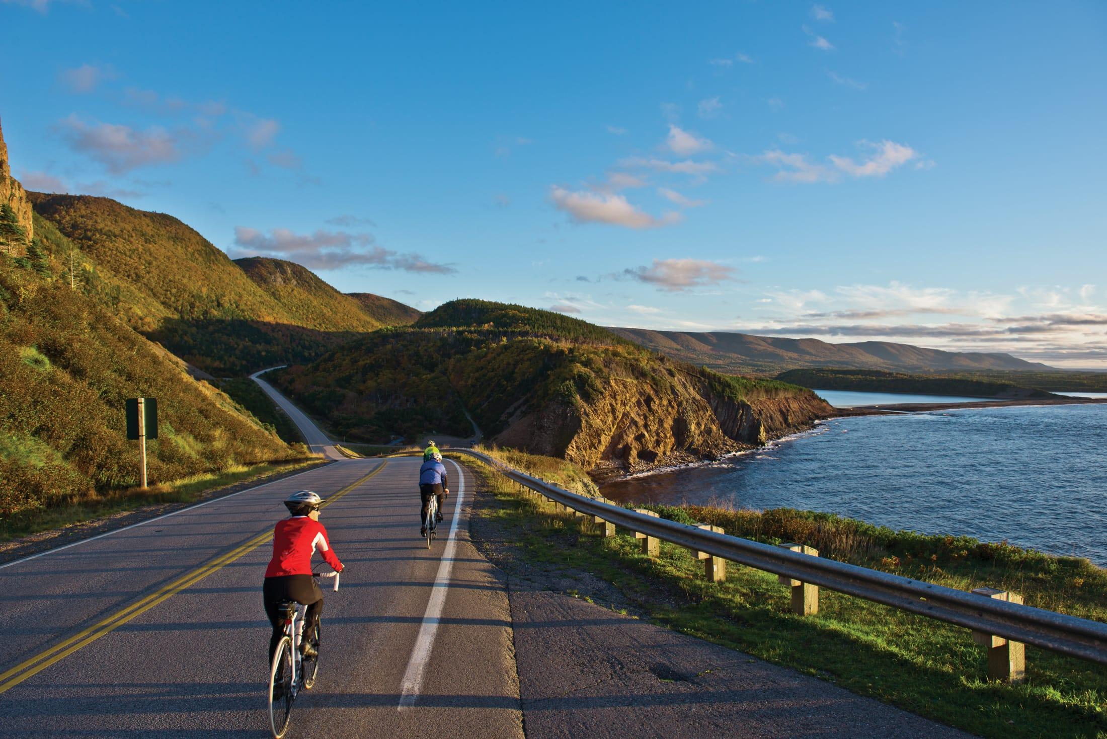 Bikers pedal down the highway overlooking the ocean