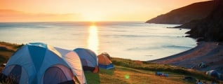 Multiple tents pitched on a hill overlooking the ocean at sunset