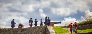 Men in period clothing shoot cannons at a historic site