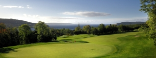 A rolling green golf course overlooking the ocean