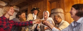 Six people wrapped around a pub table, taking a shot of whiskey in celebration