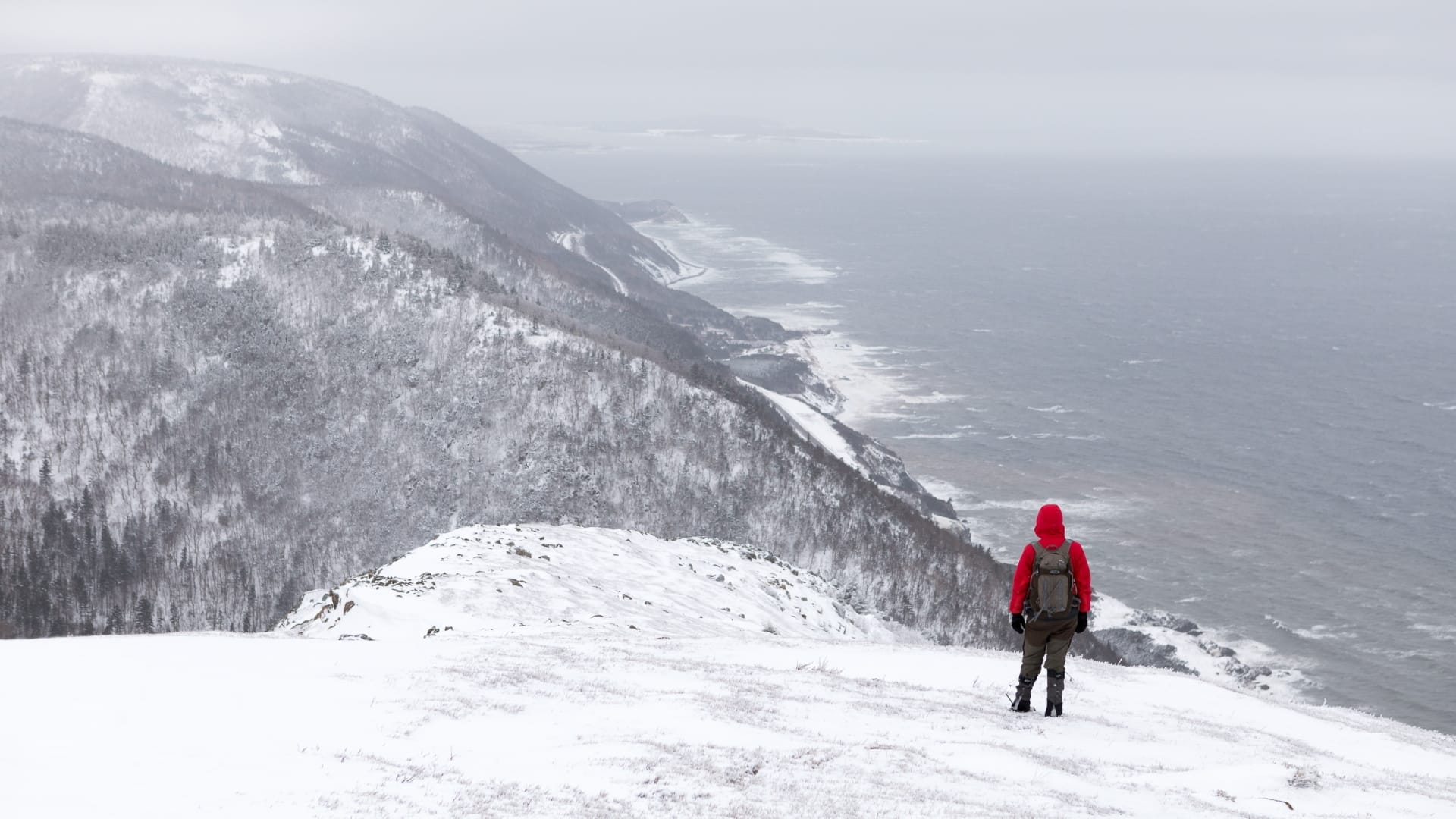 A hiker stands on a snowy hill overlooking the ocean