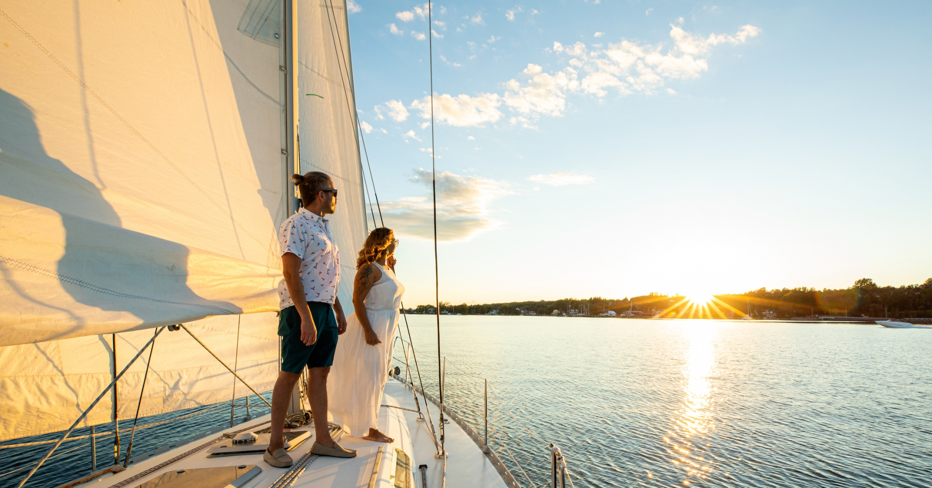a couple stands on a sailboat looking at the setting sun