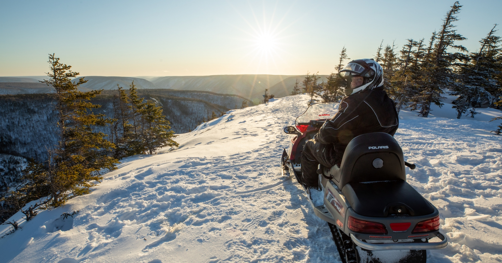 Snowmobiler overlooking the snowy highlands