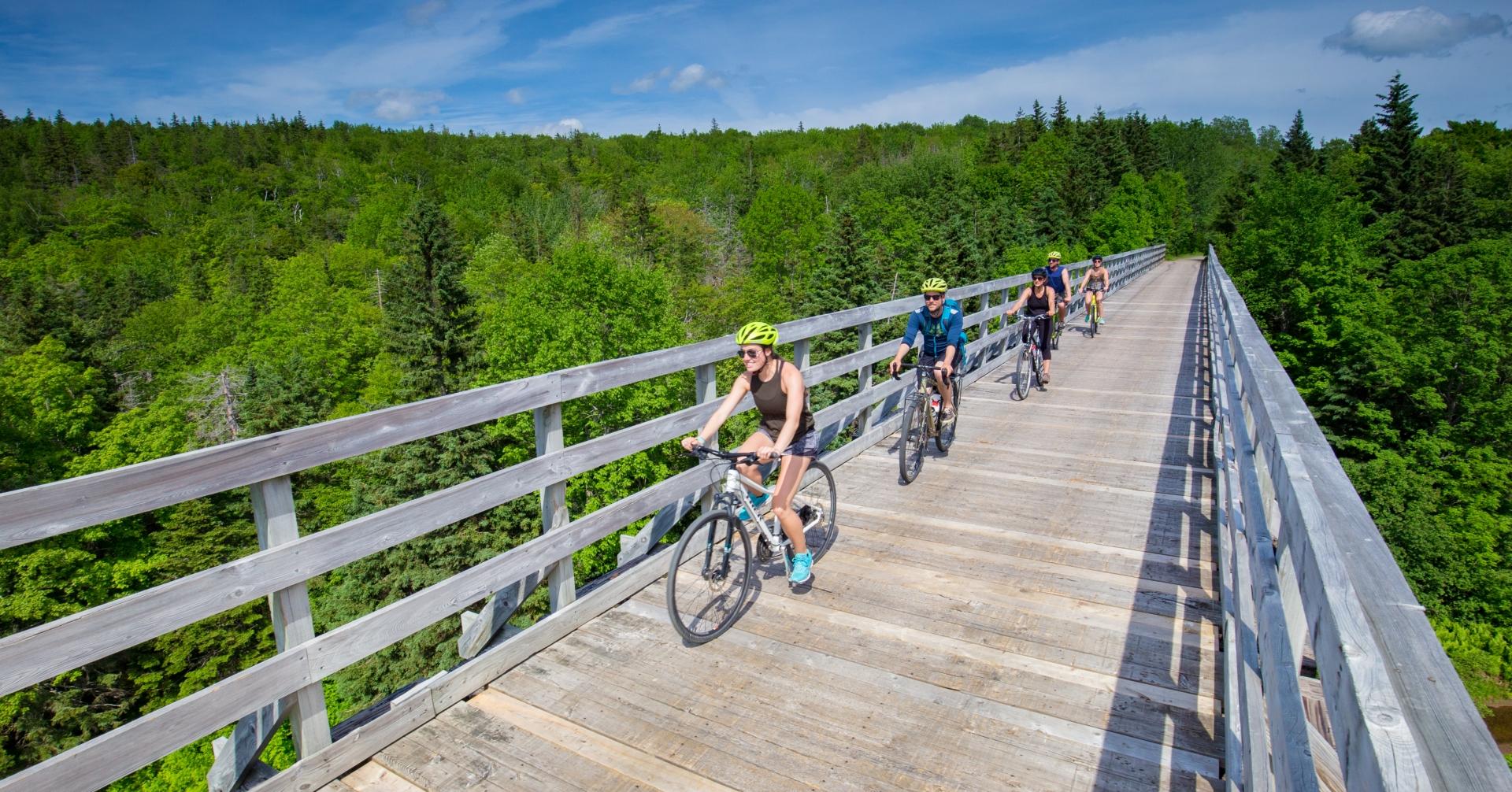 five riders bike along a long wooden bridge
