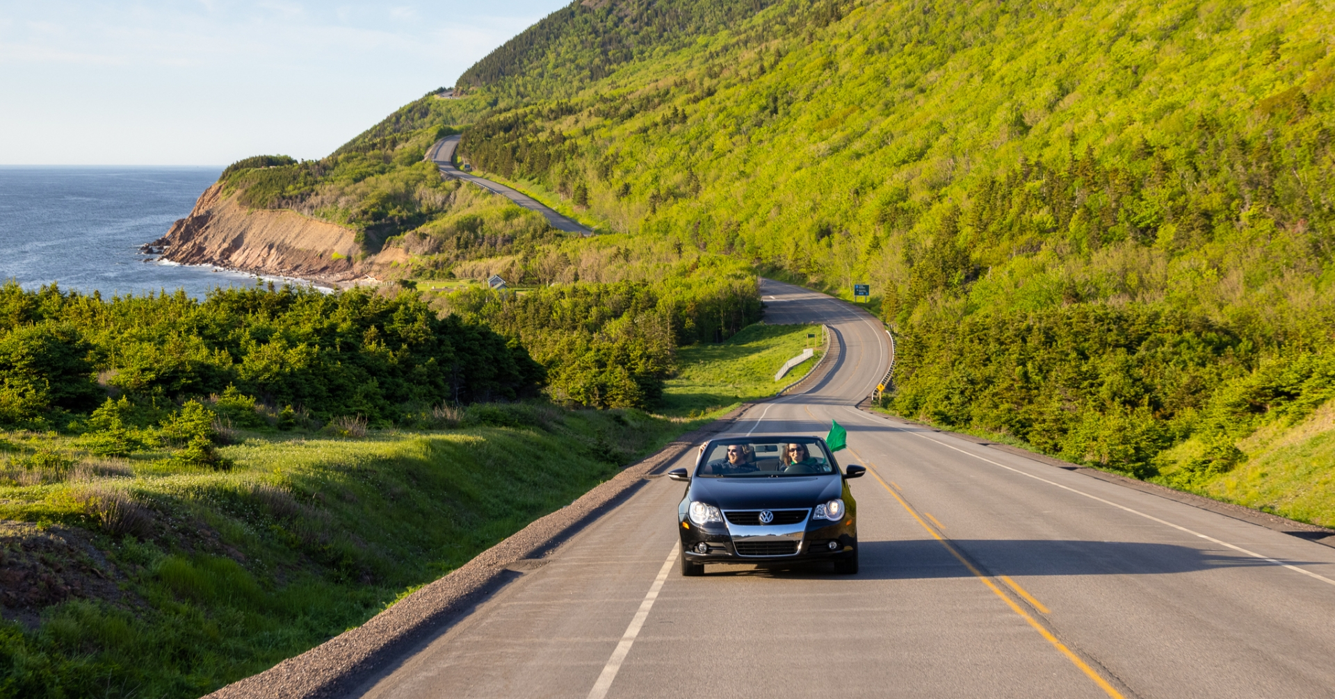 a convertible drives the Cabot Trail