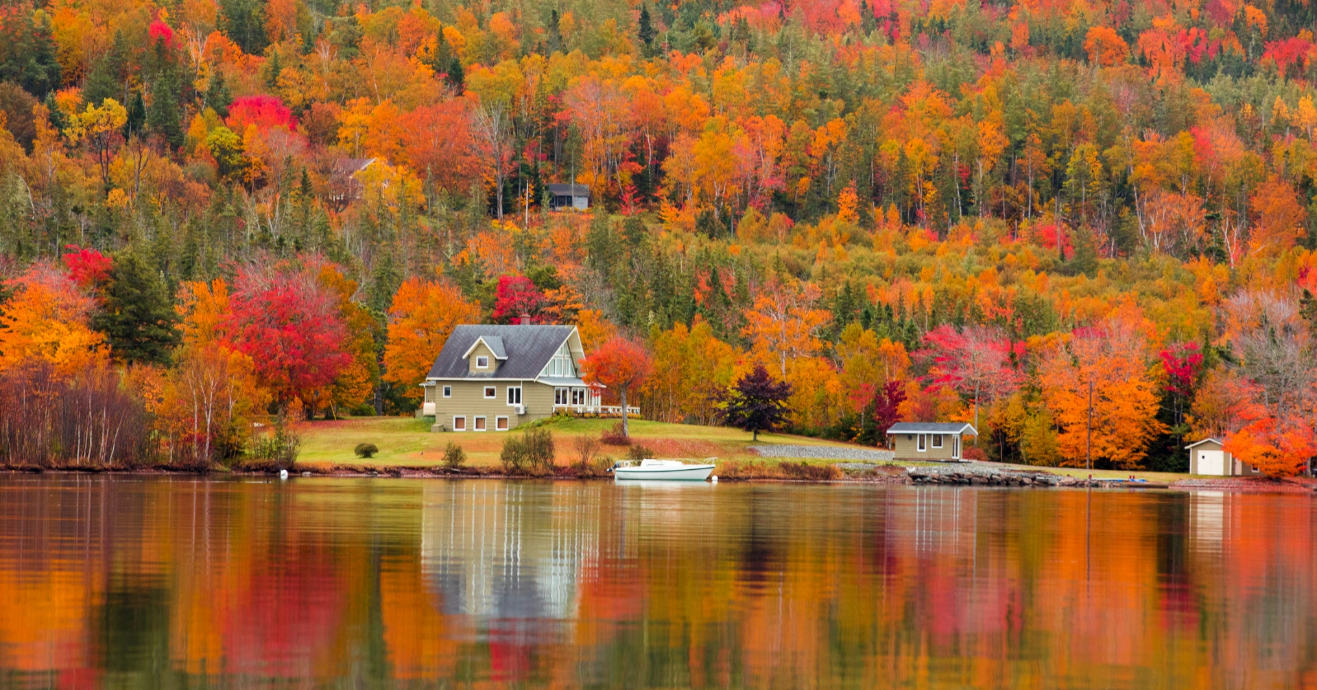 house sits by lake with vibrant autumnal trees around